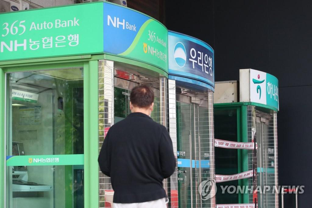 A citizen passes by a row of ATM machines in Seoul. (Yonhap)
