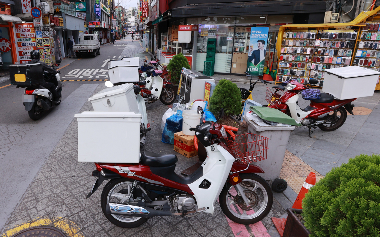 Delivery service rider drives by a street in Seoul on Tueday afternoon. (Yonhap)