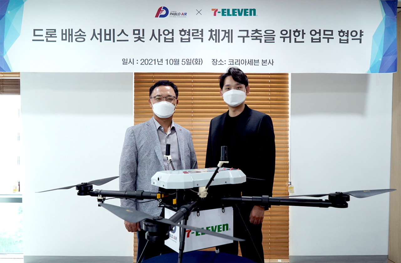 Seven Eleven CEO Choi Kyung-ho, (left) poses with Kim Young-joon, CEO of Pablo Air at the convenience store chain's headquarters in Seoul, on Wednesday. (Seven Eleven)