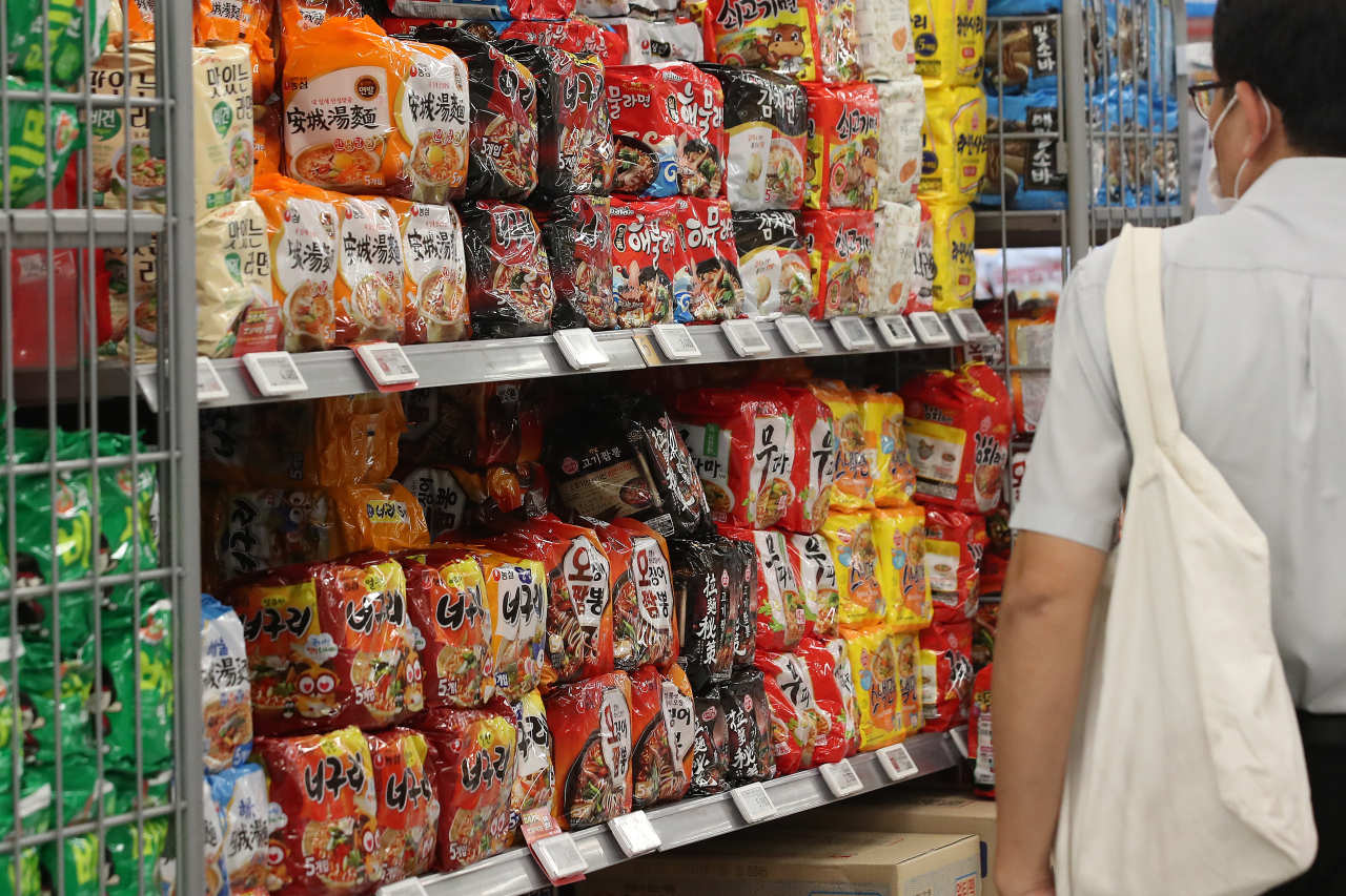 A man walks by packaged instant noodle products stacked on the shelves of a discount store. (Yonhap)
