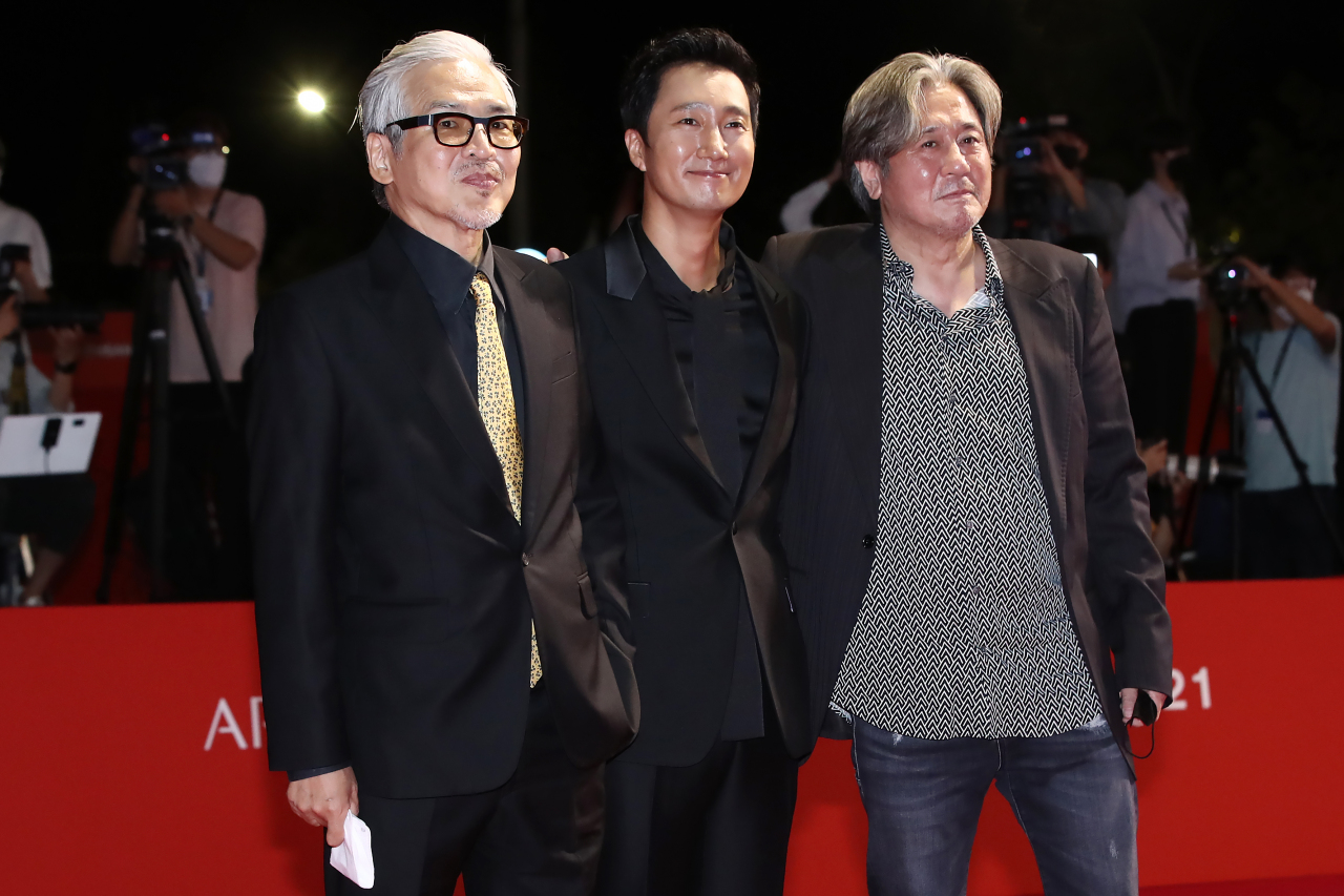 From left: Im Sang-soo, Park Hye-il and Choi Min-sik pose on the red carpet before entering the Busan Cinema Center for the 26th Busan International Film Festival's opening ceremony on Wednesday night. (Yonhap)