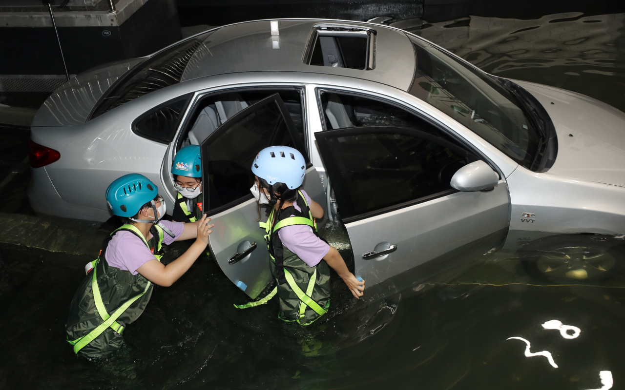 Students learn how to safely evacuate a car in heavy rain.