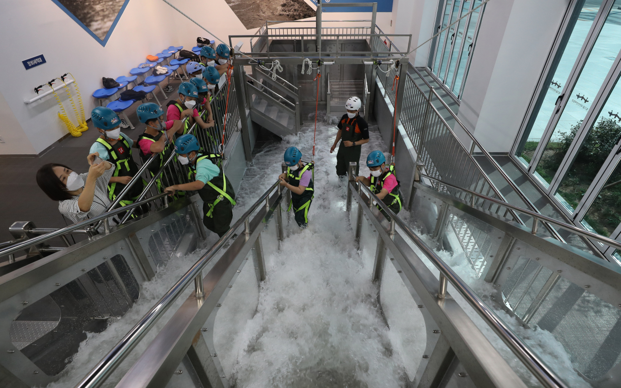 Students learn how to safely climb up stairs during heavy rain.