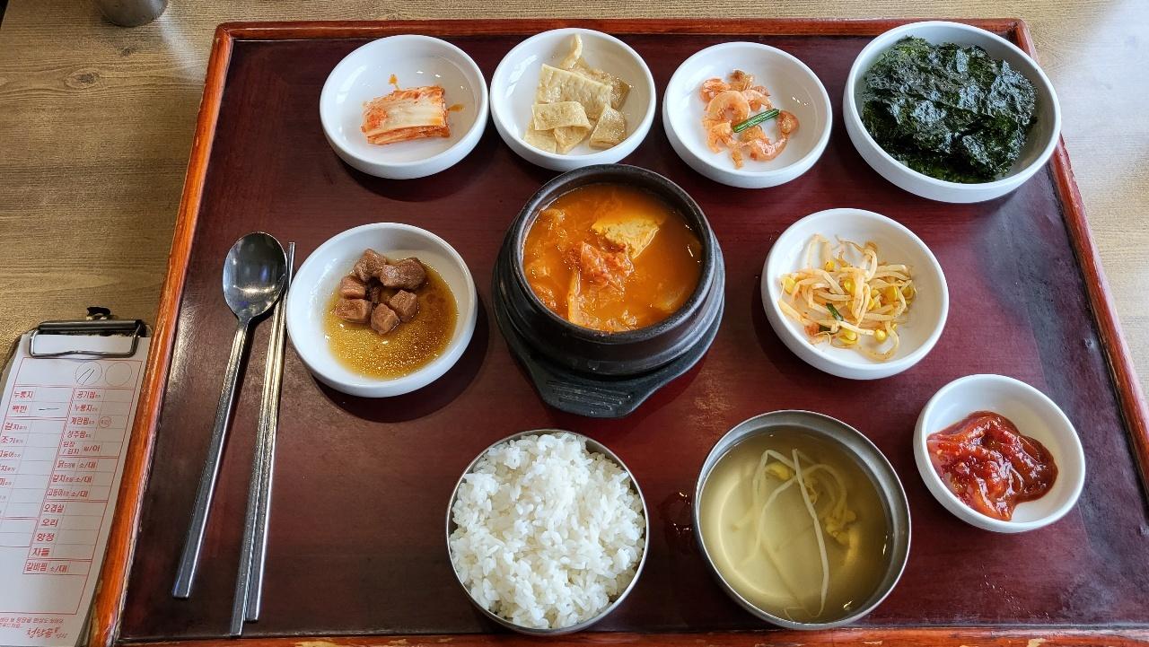 The Cheongdamgol (From top-left to bottom-right) baechu kimchi(cabbage kimchi), eomuk bokkeum(stir-fried fish cake), geonsaeu bokkeum(stir-fried dried shrimp), gim gui(roasted seaweed), dwaejigogi jangjolim(soy sauce braised pork), dubu gimchijjigae (kimchi stew with tofu), kongnamul muchim (seasoned soybean sprouts), ojingeojeot (salted squid), kongnamulguk (soybean sprout soup) (Kim Hae-yeon/ The Korea Herald)