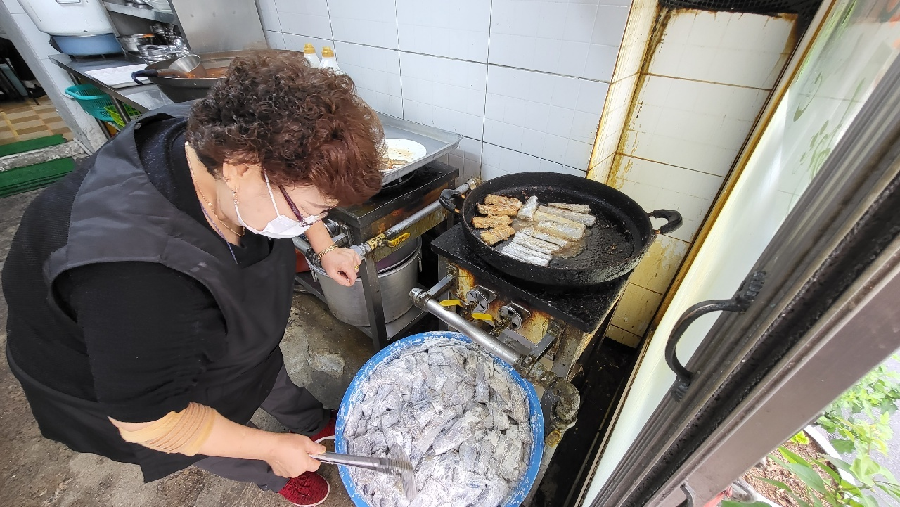 (Yangji sikdang owner) Pyun Soon-ja, owner-chef of Yangji sikdang, prepares galchigui, pan-fried cutlassfish. (Kim Hae-yeon/ The Korea Herald)