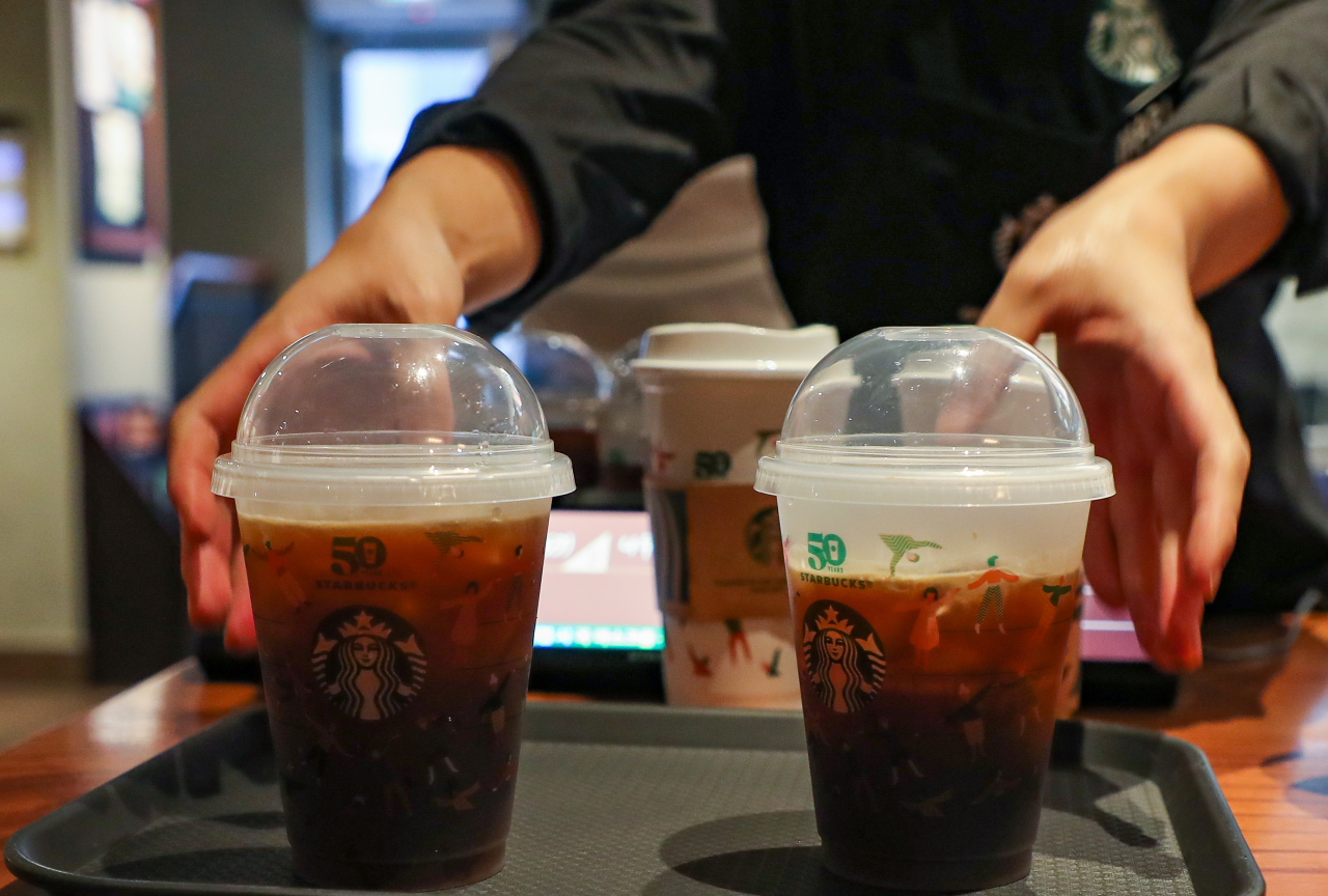 A Starbucks employee serves coffee in a reusable cup at a location in Seoul. (Yonhap)