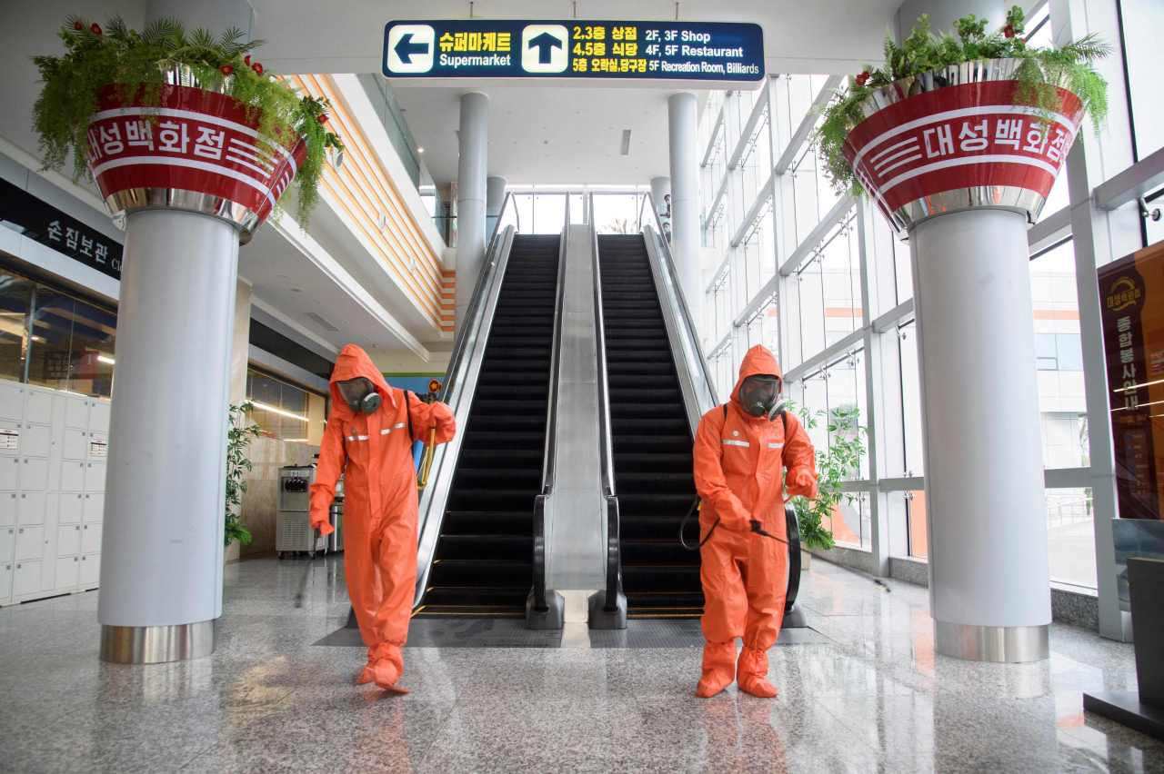 Health officials spray disinfectant as part of preventative measures against COVID-19 in the Daesong Department Store in Pyongyang on September 27. (AFP-Yonhap)