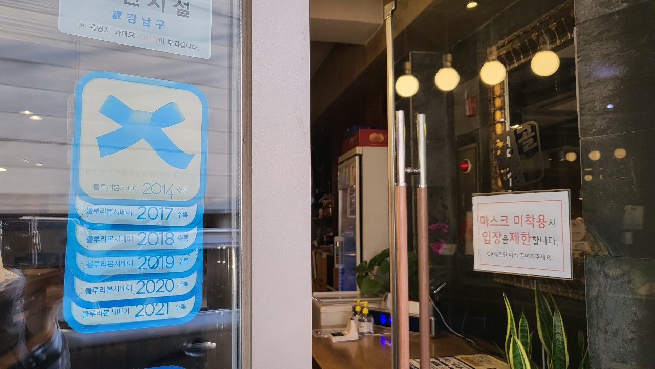 Award-winning restaurant stickers given by Blue Ribbon Survey are posted at the entrance of Cheongdamgol. (Kim Hae-yeon/ The Korea Herald)