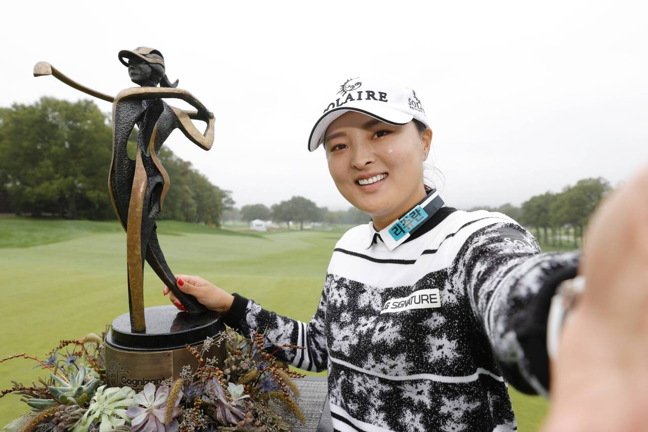 In this Getty Images photo, Ko Jin-young of South Korea imitates taking a selfie with the champion's trophy after winning the Cognizant Founders Cup at Mountain Ridge Country Club in West Caldwell, New Jersey, on Sunday. (Getty Images)