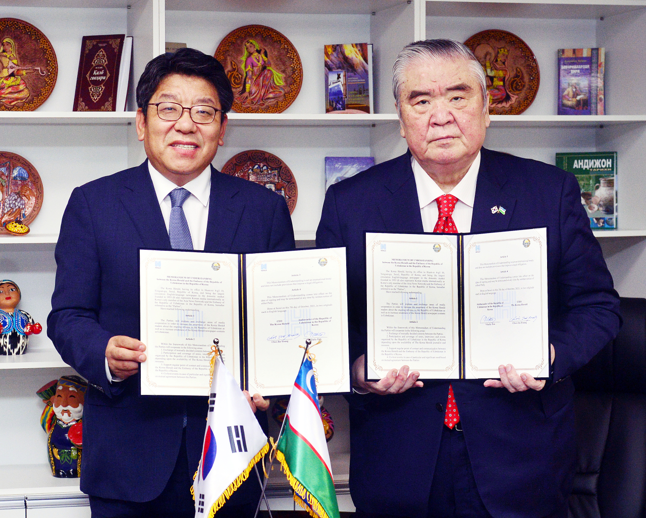 Choi Jin-young (left), CEO of The Korea Herald, poses with Uzbek Ambassador Vitali V. Fen at a signing ceremony at the Embassy of Uzbekistan in Seoul on Thursday. (Park Hyun-koo/The Korea Herald)