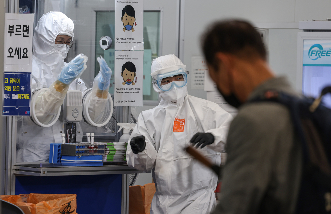 This photo taken Oct. 8 shows health care workers in protective suits at a testing center in Songpa, southern Seoul. (Yonhap)
