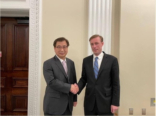 South Korea's National Security Adviser Suh Hoon (L) and his US counterpart, Jake Sullivan, are seen posing for a photo during their meeting in Washington on Tuesday in this photo provided by the South Korean embassy in Washington. (South Korean embassy)