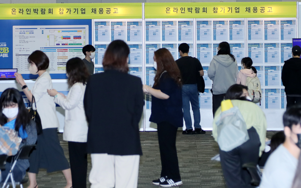 Young jobseekers look at employment information at a job fair in Goyang, north of Seoul, last Thursday. (Yonhap)