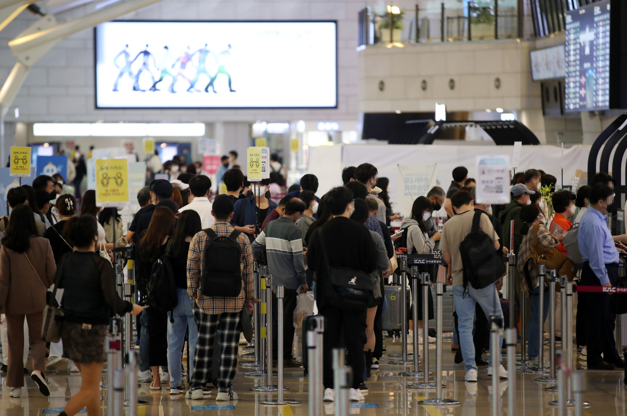 People stand in line for their flights at Gimpo International Airport in western Seoul last Friday. (Yonhap)