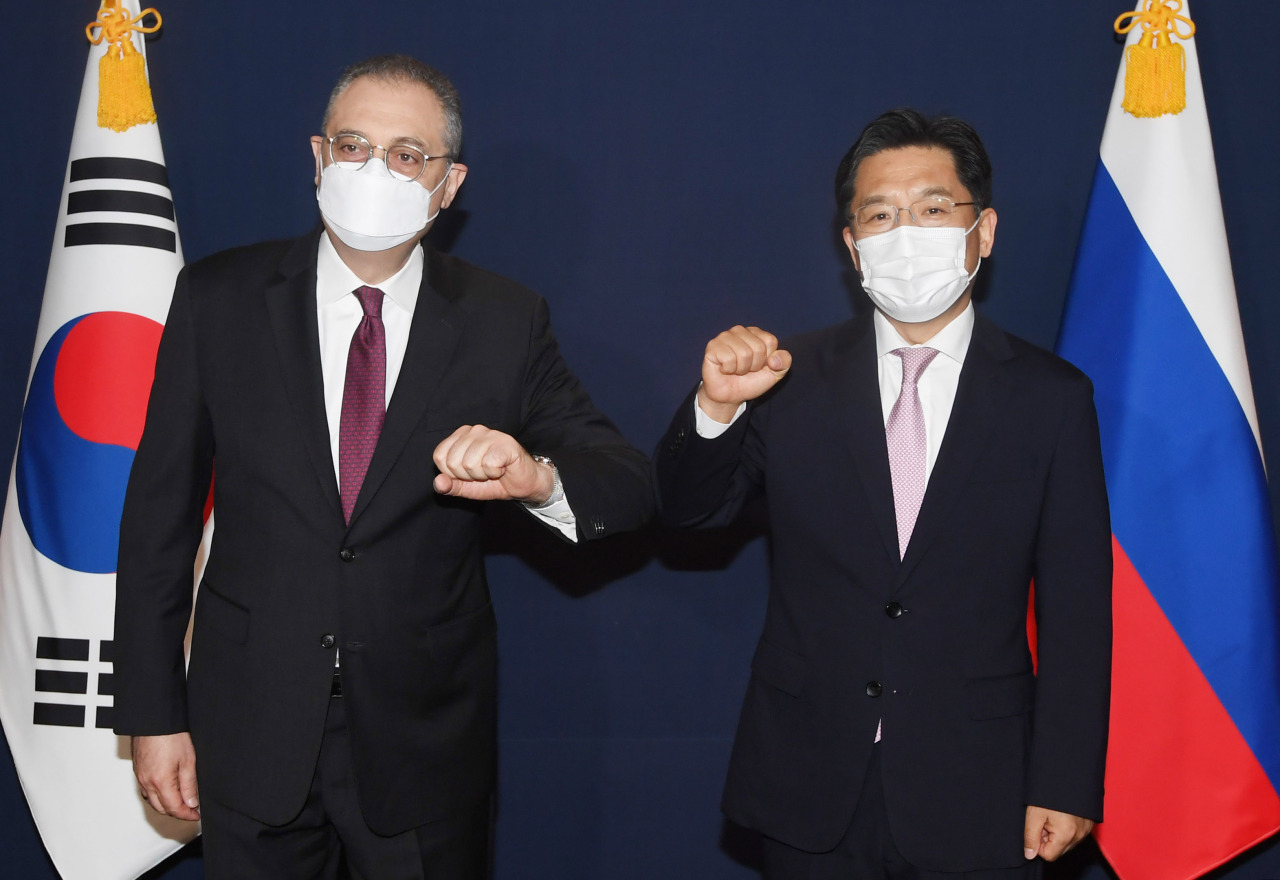 South Korea's chief nuclear envoy Noh Kyu-duk (right) elbow-bumps with Russian Deputy Foreign Minister Igor Morgulov during their talks at a hotel in Seoul on Tuesday. (Yonhap)