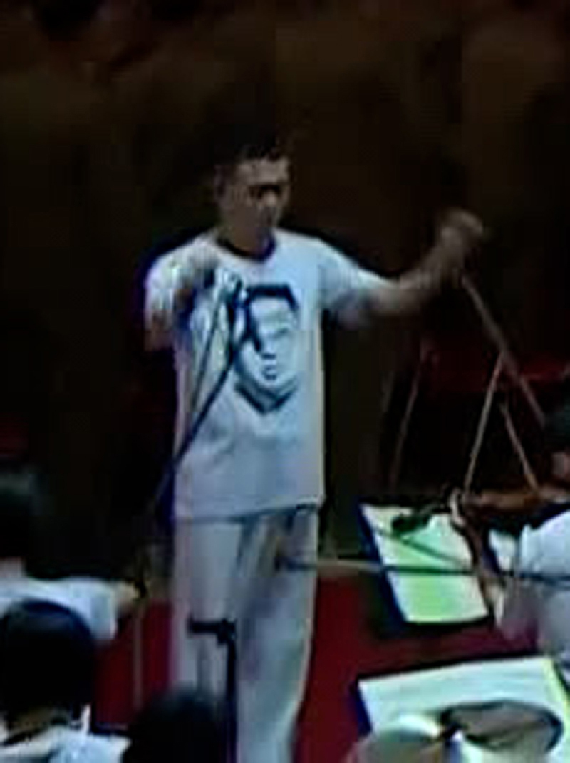 This image, captured from North Korea's official Korean Central TV Broadcasting Station, shows an orchestra conductor wearing a T-shirt printed with the portrait of the North's leader Kim Jong-un during a defense expo in Pyongyang on Monday. (North Korea's official Korean Central TV Broadcasting Station)