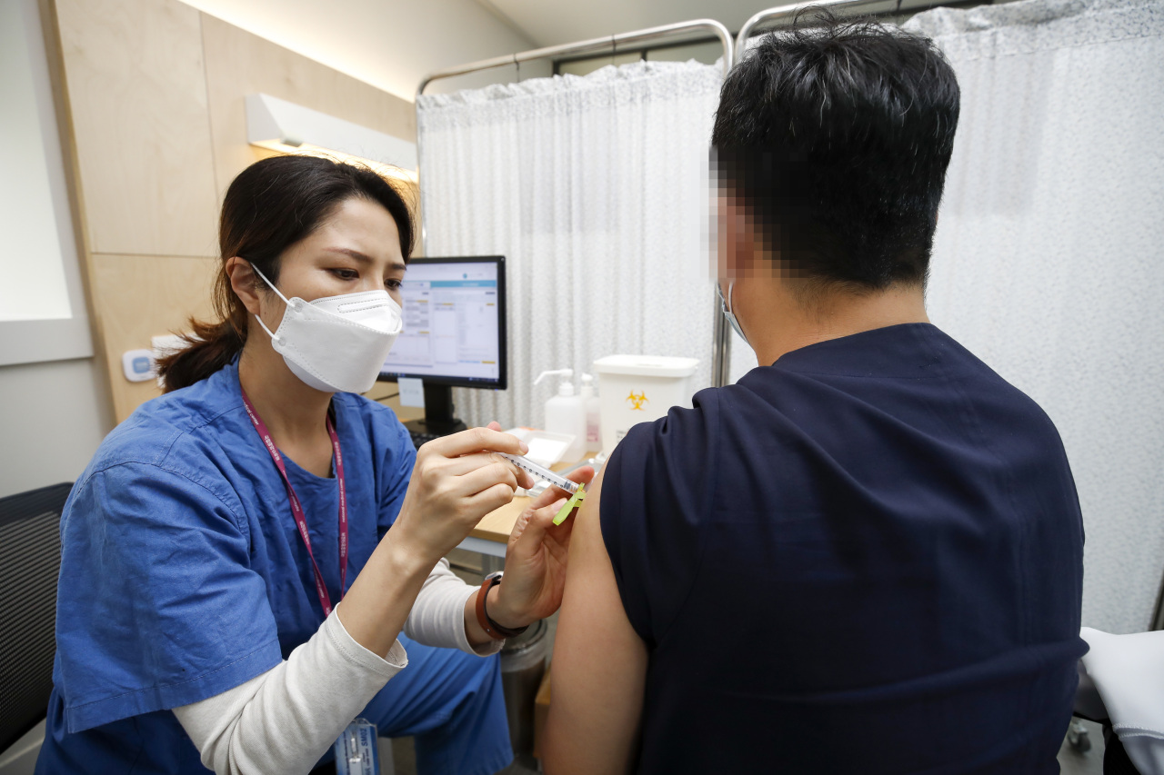 A health care worker at the National Medical Center in Seoul administers a dose of a COVID-19 vaccine on Tuesday. (Yonhap)