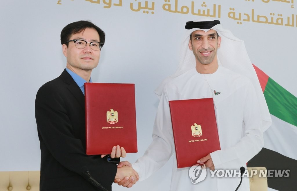 South Korean Trade Minister Yeo Han-koo (L) and United Arab Emirates Minister of State for Foreign Trade Thani Ahmed Al Zeyoudi shake hands after signing an agreement to push for a Comprehensive Economic Partnership Agreement in Dubai on Oct. 14, 2021, in this photo released by the Ministry of Trade, Industry and Energy. (Yonhap)