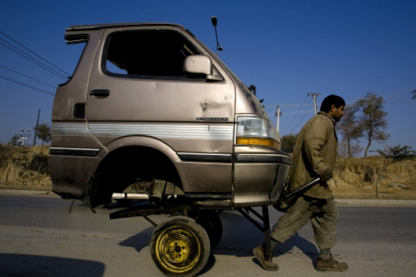 A Pakistani laborer transporting the front portion of a van