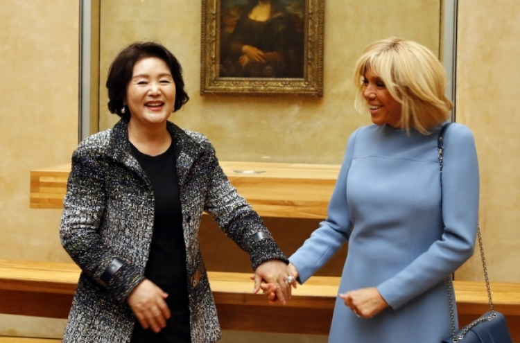 First ladies of South Korea and France walk arm in arm