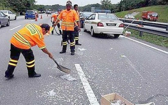 Motorists risk lives to collect coins strewn on highway