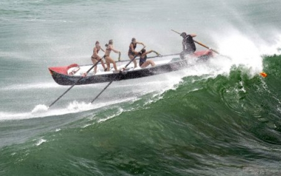Women's surf boat hit by big wave