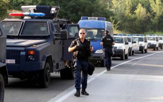Kosovo police units wait near blockades set up by Kosovo Serbs on the Leposavic-Mitrovica road on Tuesday. AFP-Yonhap News