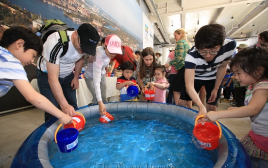 Children carry buckets of love for water charity