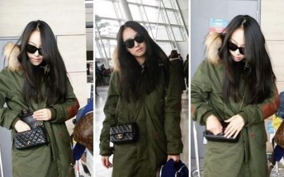 Victoria strolls through airport in khaki jacket