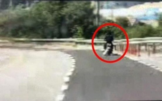 Man on motorcycle drags dog by leash