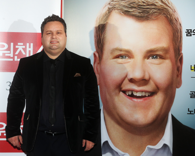 Paul Potts standing in an entire black attire in front of his portrait
