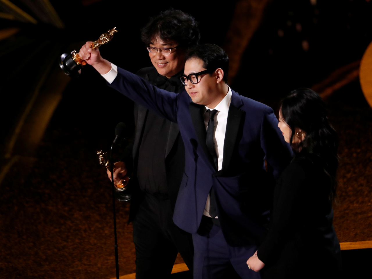 South Korean screenwriter Han Jin-won (center) and South Korean film director Bong Joon-ho accept the award for Best Original Screenplay for
